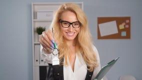 Έννοια της πώλησης και μίσθωση της ακίνητης περιουσίας Το Realtor δίνει τα κλειδιά σε ένα διαμέρισμα στους πελάτες απόθεμα βίντεο