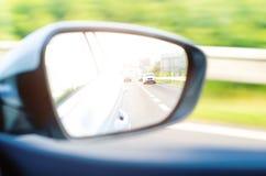 Έννοια της ταχύτητας δρόμος οδήγησης αυτοκι&n Αντανάκλαση σε έναν καθρέφτη αυτοκινήτων Οπισθοσκόπος αντανάκλαση καθρεφτών ανασκόπ Στοκ Φωτογραφία