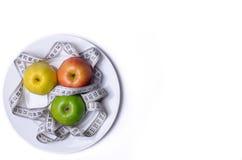 Έννοια της υγιούς κατανάλωσης, των φρέσκων μήλων σε ένα πιάτο και μια μέτρηση Στοκ Εικόνες