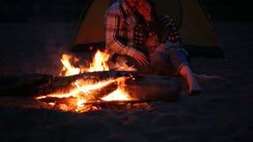 Έννοια της φιλίας, της αγάπης και των σχέσεων Νέα ευτυχής συνεδρίαση ζεύγους με την πυρά προσκόπων στην παραλία τη νύχτα απόθεμα βίντεο