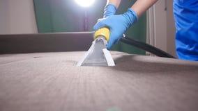 Έννοια του καθαρισμού στο διαμέρισμα και το γραφείο Εργαζόμενος στεγνού καθαρισμού που αφαιρεί το ρύπο από τον καναπέ στο εσωτερι απόθεμα βίντεο