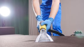 Έννοια του καθαρισμού στο διαμέρισμα και το γραφείο Εργαζόμενος στεγνού καθαρισμού που αφαιρεί το ρύπο από τον καναπέ στο εσωτερι φιλμ μικρού μήκους