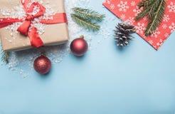 Έννοια του νέου έτους, τυλιγμένο δώρο με τα παιχνίδια και τους κώνους Χριστουγέννων, σε ένα μπλε υπόβαθρο, θέση για το κείμενο στοκ εικόνες