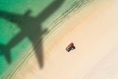 Έννοια του ταξιδιού αεροπλάνων στον εξωτικό προορισμό με τη σκιά του εμπορικού αεροπλάνου που πετά επάνω από την όμορφη τροπική π στοκ φωτογραφίες