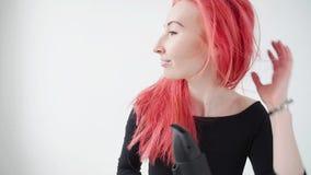 Έννοια του χρωματισμού και της προσοχής τρίχας Η νέα γυναίκα ξεραίνει την κόκκινη τρίχα σε ένα άσπρο υπόβαθρο απόθεμα βίντεο