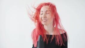 Έννοια του χρωματισμού και της προσοχής τρίχας Η νέα γυναίκα ξεραίνει την κόκκινη τρίχα σε ένα άσπρο υπόβαθρο φιλμ μικρού μήκους