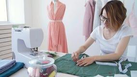 Έννοια του χόμπι και της μικρής επιχείρησης Ο νέος θηλυκός σχεδιαστής σχεδιάζει τα ενδύματα σε ένα φωτεινό εργαστήριο στούντιο απόθεμα βίντεο