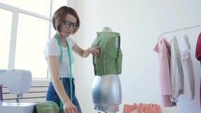 Έννοια του χόμπι και της μικρής επιχείρησης Ο νέος θηλυκός σχεδιαστής σχεδιάζει τα ενδύματα σε ένα φωτεινό εργαστήριο στούντιο φιλμ μικρού μήκους
