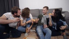 Έννοια τροφίμων, ελεύθερου χρόνου και ευτυχίας - τέσσερις χαμογελώντας νέοι που τρώνε την πίτσα στο σπίτι και που πίνουν μια μπύρ απόθεμα βίντεο