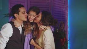 Έννοια των ευτυχών οικογενειακών γονέων που φιλούν το υπόβαθρο Χριστουγέννων κορών του απόθεμα βίντεο