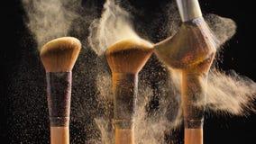 Έννοια των καλλυντικών και της ομορφιάς Βούρτσες με τη χρυσή καλλυντική σκόνη απόθεμα βίντεο