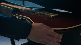 Έννοια των μουσικών οργάνων Ένα άτομο ανοίγει την περίπτωση με μια κιθάρα απόθεμα βίντεο