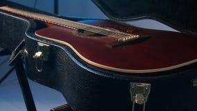 Έννοια των μουσικών οργάνων Ένα άτομο ανοίγει την περίπτωση με μια κιθάρα φιλμ μικρού μήκους