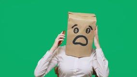 Έννοια των συγκινήσεων, χειρονομίες ένα άτομο με τις τσάντες εγγράφου στο κεφάλι του, με χρωματισμένη emoticon, φόβος Ομιλία σε έ απόθεμα βίντεο