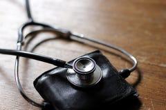Έννοια υγείας πορτοφολιών - που χρησιμοποιεί ένα στηθοσκόπιο Στοκ Φωτογραφίες