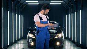 Έννοια υπηρεσιών αυτοκινήτων Αυτοκίνητο-προσοχή με τον αρσενικό τεχνικό που γράφει μια έκθεση φιλμ μικρού μήκους