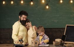 Έννοια υποστήριξης γονέα Γονείς που προσέχουν το σχέδιο γιων τους, που μαθαίνει να γράφει, πίνακας κιμωλίας στο υπόβαθρο Αγόρι σε στοκ φωτογραφία