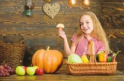 Έννοια φεστιβάλ συγκομιδών Κορίτσι παιδιών που παρουσιάζει τη συγκομιδή του φυτικού κήπου της στο ξύλινο υπόβαθρο Το κορίτσι παιδ στοκ φωτογραφίες