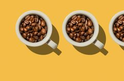 Έννοια φλυτζανιών Άσπρα φλυτζάνια με τα φασόλια καφέ στο κίτρινο υπόβαθρο Στοκ εικόνα με δικαίωμα ελεύθερης χρήσης