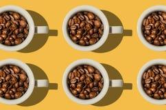 Έννοια φλυτζανιών Άσπρα φλυτζάνια με τα φασόλια καφέ στο κίτρινο υπόβαθρο Στοκ Φωτογραφία