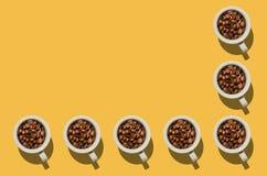 Έννοια φλυτζανιών Άσπρα φλυτζάνια με τα φασόλια καφέ στο κίτρινο υπόβαθρο Στοκ εικόνες με δικαίωμα ελεύθερης χρήσης