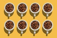 Έννοια φλυτζανιών Άσπρα φλυτζάνια με τα φασόλια καφέ στο κίτρινο υπόβαθρο Στοκ φωτογραφία με δικαίωμα ελεύθερης χρήσης