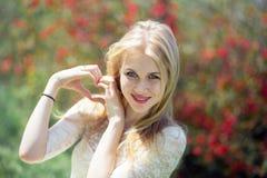 Έννοια φύσης αγάπης χειρονομίας - χαμογελώντας νέα ξανθή γυναίκα που παρουσιάζει μορφή καρδιών φιαγμένη από δάχτυλα πέρα από την  Στοκ Εικόνες