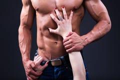 Έννοια φύλων - κλείστε επάνω των θηλυκών χεριών σχετικά με το μυϊκό αρσενικό BO Στοκ Εικόνες