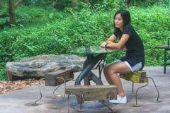 Έννοια χαλάρωσης: Η συνεδρίαση γυναικών χαλαρώνει στην ξύλινη καρέκλα στον υπαίθριο κήπο Στοκ φωτογραφία με δικαίωμα ελεύθερης χρήσης