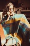 Έννοια χειμερινής κρύα ασθένειας Νέα παγώνοντας συνεδρίαση γυναικών στην άνετη σύγχρονη καρέκλα με την κούπα του τσαγιού που τυλί Στοκ Φωτογραφίες