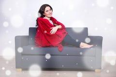 Έννοια χειμερινής χαλάρωσης - συνεδρίαση γυναικών στον καναπέ που τυλίγεται στο κόκκινο Στοκ Εικόνες