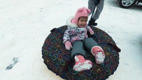 Έννοια χειμώνα, ελεύθερου χρόνου και ψυχαγωγίας - ευτυχές χαμογελώντας κορίτσι που βρίσκεται σε ένα έλκηθρο απόθεμα βίντεο