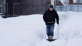 Έννοια χειμώνα και καθαρισμού - ώριμο άτομο που φτυαρίζει το χιόνι από driveway απόθεμα βίντεο