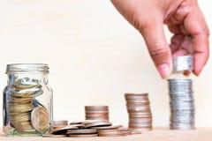 Έννοια χρημάτων αποταμίευσης με θολωμένος των νομισμάτων σωρών λαβής δάχτυλων Στοκ φωτογραφία με δικαίωμα ελεύθερης χρήσης