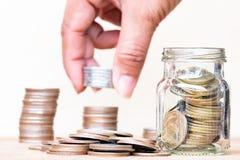 Έννοια χρημάτων αποταμίευσης με θολωμένος των νομισμάτων σωρών λαβής δάχτυλων Στοκ Εικόνα