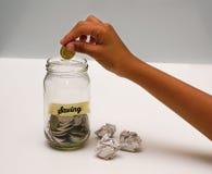Έννοια χρημάτων αποταμίευσης με την τοποθέτηση χεριών νομίσματα στο βάζο γυαλιού Εκλεκτική εστίαση και ρηχό DOF Στοκ φωτογραφίες με δικαίωμα ελεύθερης χρήσης