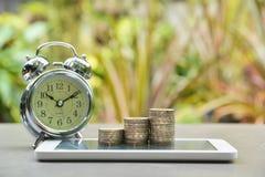 Έννοια χρημάτων αποταμίευσης με το σωρό νομισμάτων χρημάτων στο έξυπνος-τηλέφωνο στοκ φωτογραφίες με δικαίωμα ελεύθερης χρήσης