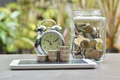 Έννοια χρημάτων αποταμίευσης με το σωρό νομισμάτων χρημάτων στο έξυπνος-τηλέφωνο στοκ εικόνα