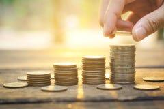 Έννοια χρημάτων αποταμίευσης με το χέρι που βάζει την αυξανόμενη επιχείρηση σωρών νομισμάτων χρημάτων στο υπόβαθρο ηλιοβασιλέματο Στοκ φωτογραφίες με δικαίωμα ελεύθερης χρήσης