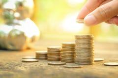 Έννοια χρημάτων αποταμίευσης με το χέρι που βάζει την αυξανόμενη επιχείρηση σωρών νομισμάτων χρημάτων στο υπόβαθρο ηλιοβασιλέματο Στοκ Εικόνα