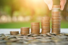 Έννοια χρημάτων αποταμίευσης με το χέρι που βάζει την αυξανόμενη επιχείρηση σωρών νομισμάτων χρημάτων στο υπόβαθρο ηλιοβασιλέματο Στοκ εικόνα με δικαίωμα ελεύθερης χρήσης