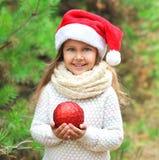 Έννοια Χριστουγέννων - λίγο χαμογελώντας παιδί κοριτσιών στο κόκκινο καπέλο santa με τη σφαίρα Στοκ φωτογραφία με δικαίωμα ελεύθερης χρήσης