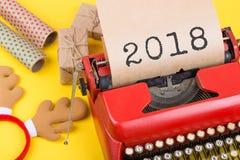 Έννοια Χριστουγέννων - γραφομηχανή με το κείμενο &#x22 2018&#x22 , κιβώτια δώρων και τυλίγοντας έγγραφο για το κίτρινο υπόβαθρο Στοκ Εικόνες