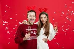 Έννοια Χριστουγέννων - ευτυχείς καυκάσιοι άνδρας και γυναίκα στα καπέλα ταράνδων που γιορτάζουν το ψήσιμο Χριστουγέννων με τα φλά Στοκ Εικόνα