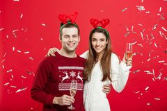 Έννοια Χριστουγέννων - ευτυχείς καυκάσιοι άνδρας και γυναίκα στα καπέλα ταράνδων που γιορτάζουν το ψήσιμο Χριστουγέννων με τα φλά Στοκ φωτογραφία με δικαίωμα ελεύθερης χρήσης
