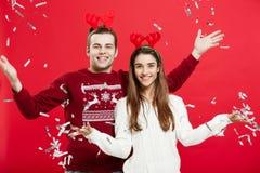 Έννοια Χριστουγέννων - ευτυχείς καυκάσιοι άνδρας και γυναίκα στα καπέλα ταράνδων που γιορτάζουν το ψήσιμο Χριστουγέννων με τα φλά Στοκ εικόνες με δικαίωμα ελεύθερης χρήσης