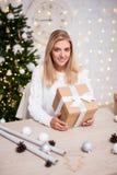 Έννοια Χριστουγέννων - νέα όμορφη ξανθή συνεδρίαση γυναικών με το GIF στοκ εικόνα