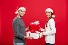 Έννοια Χριστουγέννων - νέο ελκυστικό ζεύγος που δίνει τα δώρα που γιορτάζουν ο ένας στον άλλο στη ημέρα των Χριστουγέννων Στοκ φωτογραφίες με δικαίωμα ελεύθερης χρήσης