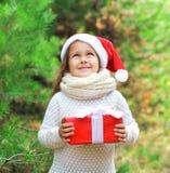 Έννοια Χριστουγέννων - χαμογελώντας παιδί στο κόκκινο καπέλο santa με το δώρο κιβωτίων Στοκ Φωτογραφία