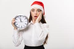 Έννοια χρονικής διαχείρισης - νέα επιχειρησιακή γυναίκα με το καπέλο santa που κρατά ένα ρολόι απομονωμένο πέρα από το άσπρο υπόβ Στοκ Εικόνες